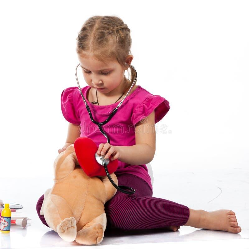Bella ragazza che gioca medico con una bambola fotografia stock