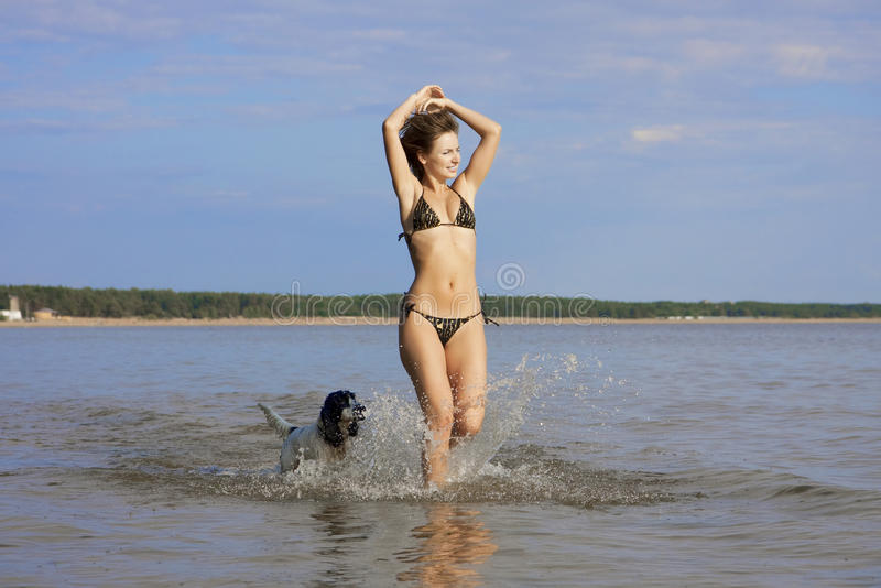 Bella ragazza che gioca sulla spiaggia con un cane fotografia stock