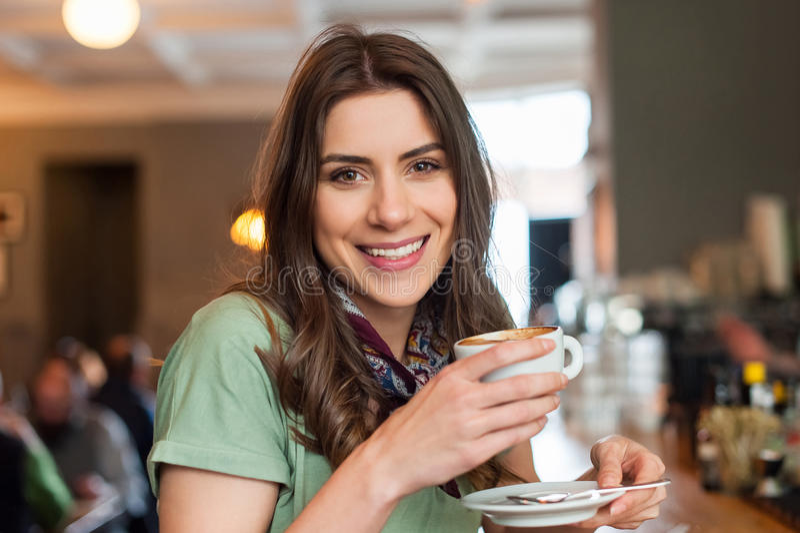 Bella ragazza che gode di buon caffè nel negozio del caffè fotografie stock