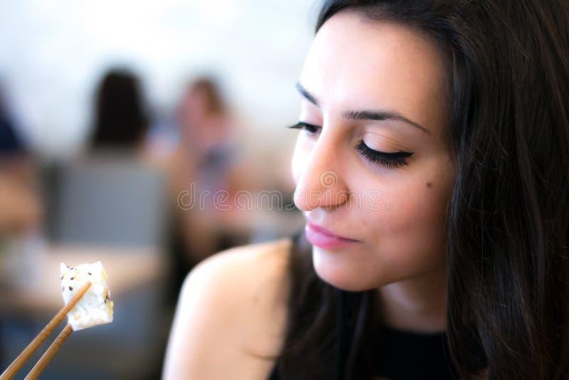 Bella ragazza che guarda e che mangia i sushi fotografia stock libera da diritti