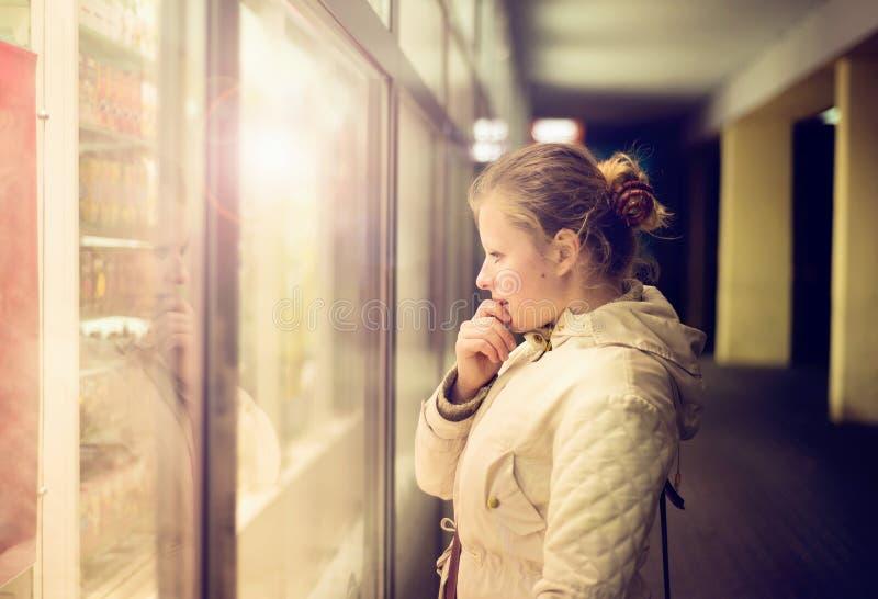 Bella ragazza che guarda nello shopwindow sulla notte fotografie stock