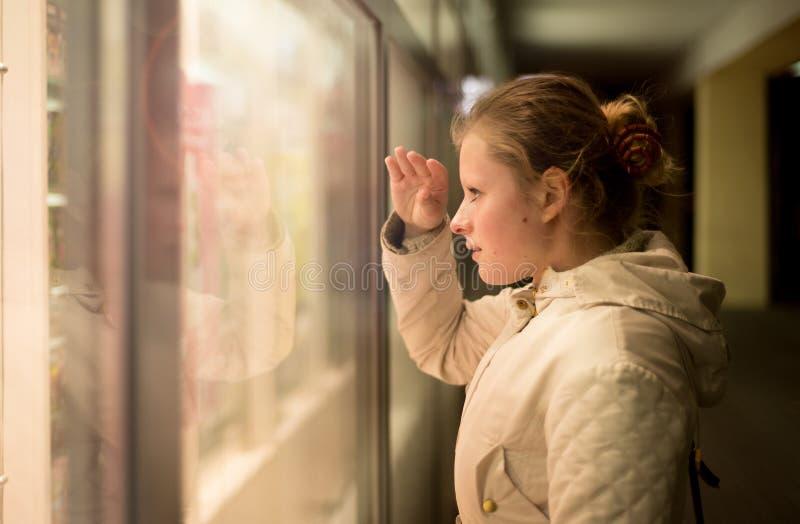 Bella ragazza che guarda nello shopwindow sulla notte fotografia stock libera da diritti