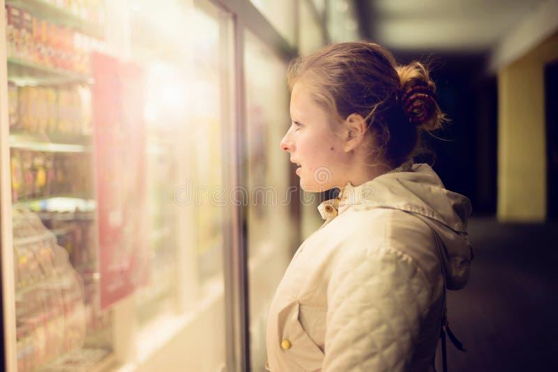Bella ragazza che guarda nello shopwindow sulla notte immagini stock libere da diritti