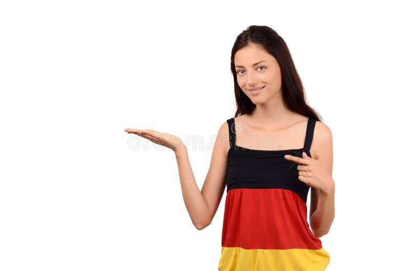 Bella ragazza che indica e che presenta. Ragazza attraente con la blusa della bandiera della Germania. fotografia stock
