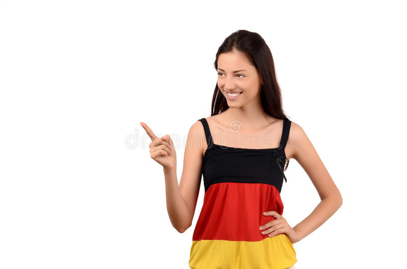 Bella ragazza che indica il lato. Ragazza attraente con la blusa della bandiera della Germania. fotografia stock libera da diritti