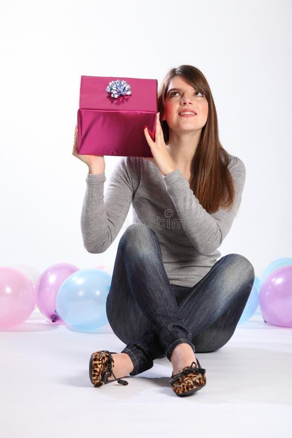 Bella ragazza che indovina il presente di compleanno di mistero fotografia stock