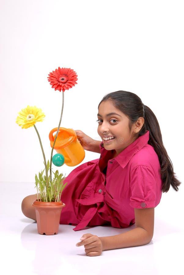 Bella ragazza che innaffia una pianta fotografie stock