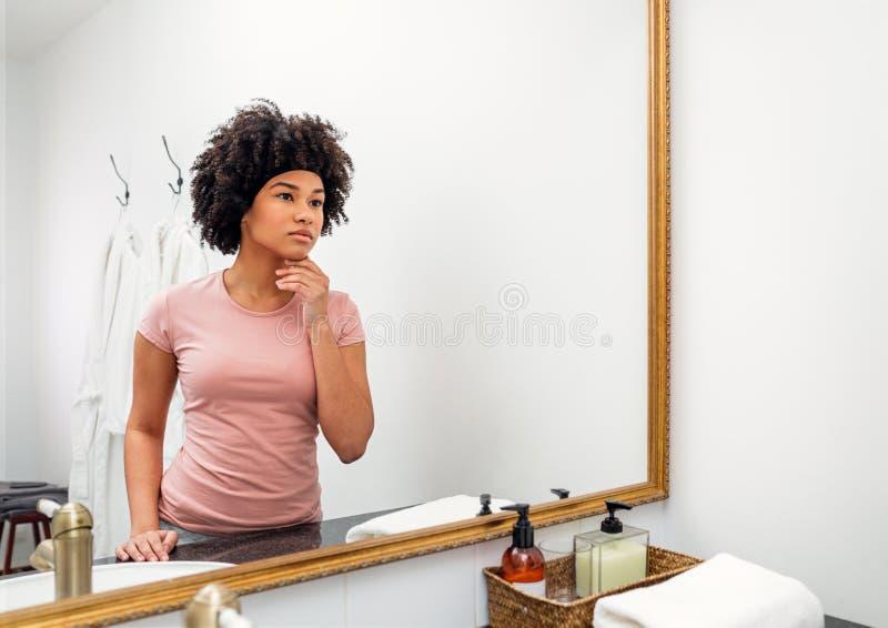 Bella ragazza che ispeziona il suo fronte immagini stock libere da diritti