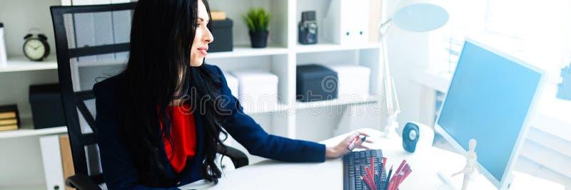Bella ragazza che lavora con il computer ed i documenti nell'ufficio alla tavola fotografia stock