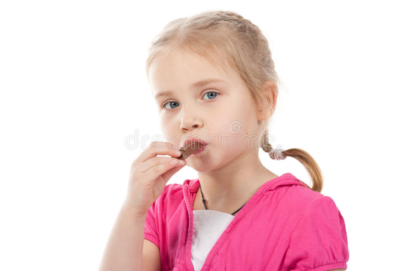 Bella ragazza che mangia la barra di cioccolato fotografia stock