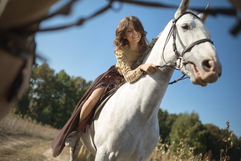 Bella ragazza che monta un cavallo fotografia stock