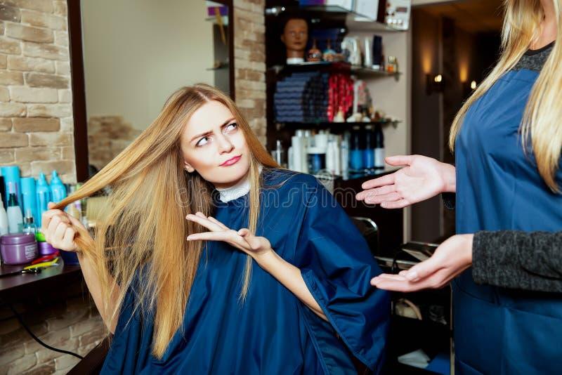 Bella ragazza che mostra i suoi capelli al parrucchiere immagini stock