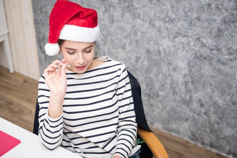 Bella ragazza che porta un cappello di Natale di Santa all'ufficio fotografie stock libere da diritti