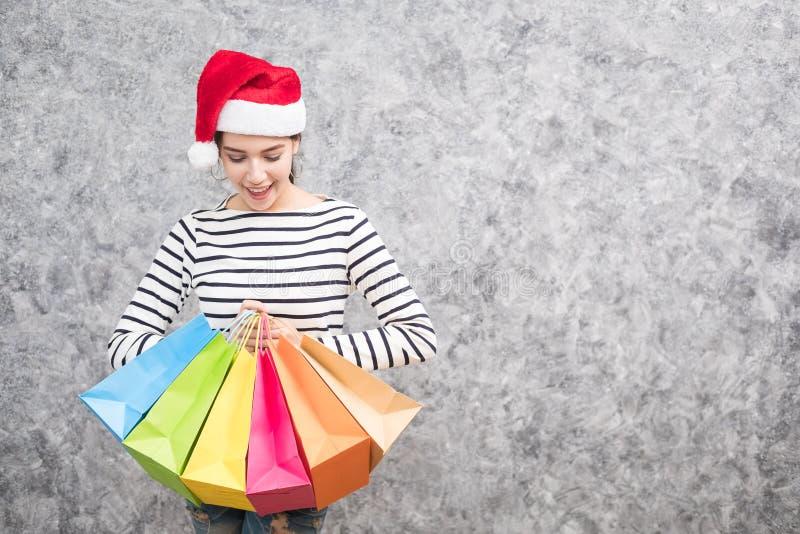 Bella ragazza che porta un cappello di Santa che tiene i lotti dei sacchetti della spesa immagini stock
