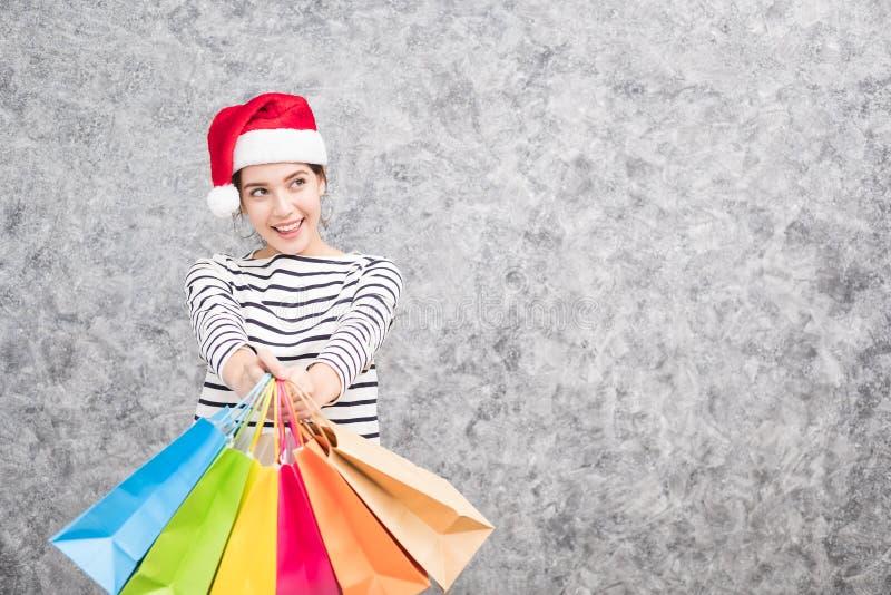 Bella ragazza che porta un cappello di Santa che tiene i lotti dei sacchetti della spesa fotografie stock libere da diritti