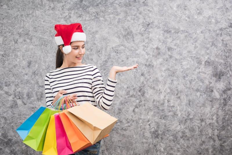 Bella ragazza che porta un cappello di Santa che tiene i lotti dei sacchetti della spesa fotografia stock