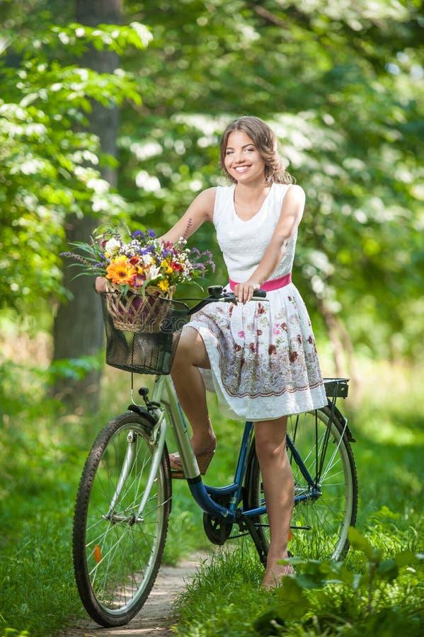Bella ragazza che porta un vestito bianco piacevole divertendosi nel parco con la bicicletta Concetto all'aperto sano di stile di fotografie stock