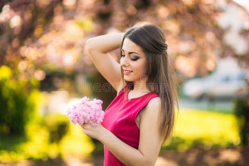 Bella ragazza che posa al fotografo contro lo sfondo degli alberi rosa di fioritura Sorgente Sakura fotografia stock