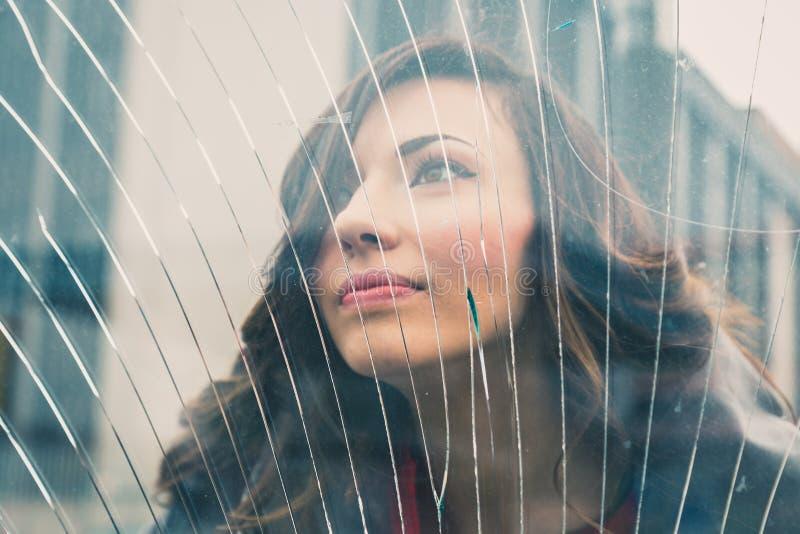 Bella ragazza che posa dietro un vetro rotto immagine stock