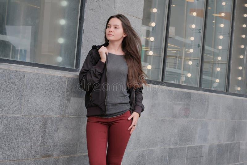 Bella ragazza che posa in vestiti caldi in autunno Rivestimento nero, jeans rossi, blusa grigia Ritratto di un modello castana sv immagine stock libera da diritti