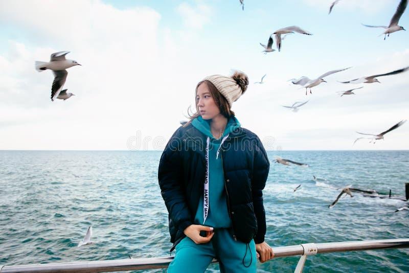 Bella ragazza che posa vicino al mare con i gabbiani fotografia stock libera da diritti