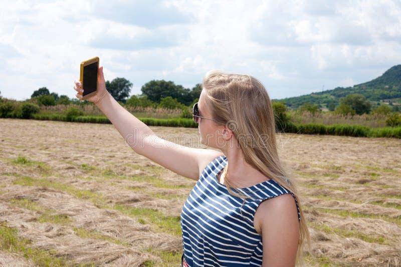 Bella ragazza che prende un selfie nella campagna fotografie stock libere da diritti