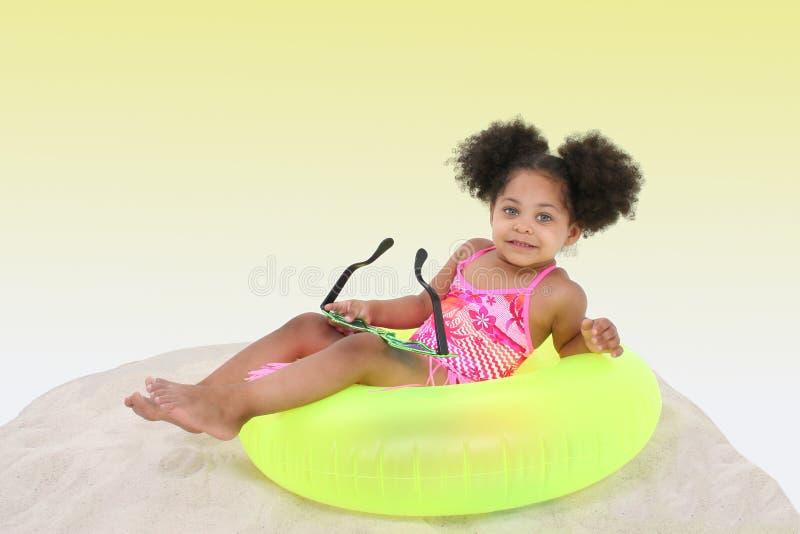 Bella ragazza che risiede nella sabbia su Floaty immagine stock