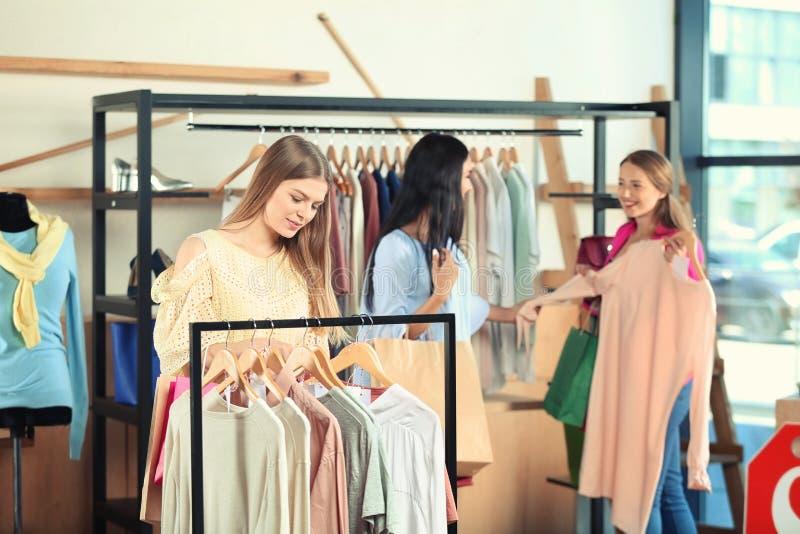 Bella ragazza che sceglie i vestiti in negozio fotografia stock libera da diritti
