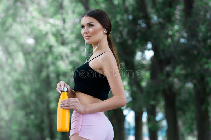 Bella ragazza che si prepara per pareggiare nel parco Con la bottiglia di termos a disposizione immagini stock libere da diritti