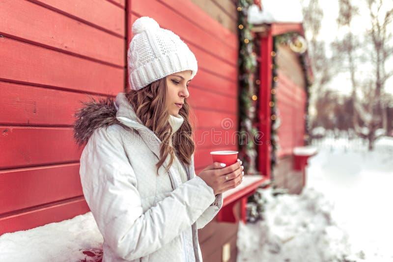 Bella ragazza che si scalda circa la tazza rossa con la bevanda calda del tè del caffè, inverno fuori Fine settimana di riposo de immagine stock