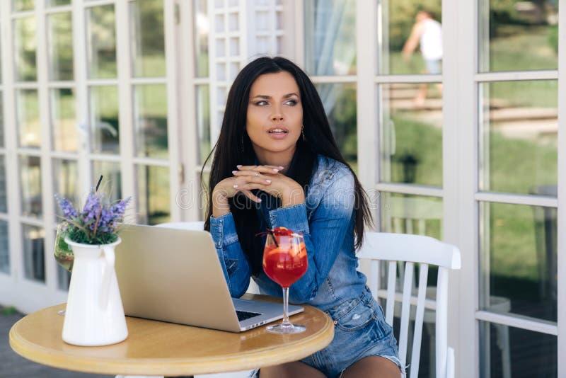 Bella ragazza che si siede ad una tavola in un caffè, esaminante il lato Il modello ha una pelle abbronzata di carnagione scura,  fotografie stock libere da diritti