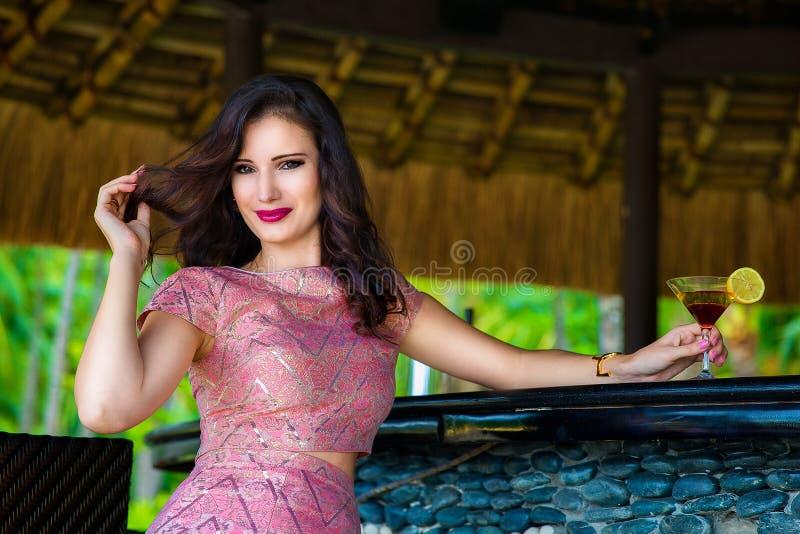 Bella ragazza che si siede alla barra dell'hotel su un isl tropicale immagini stock libere da diritti