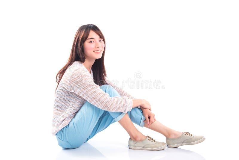 Bella ragazza che si siede e che sorride sopra il bianco fotografie stock