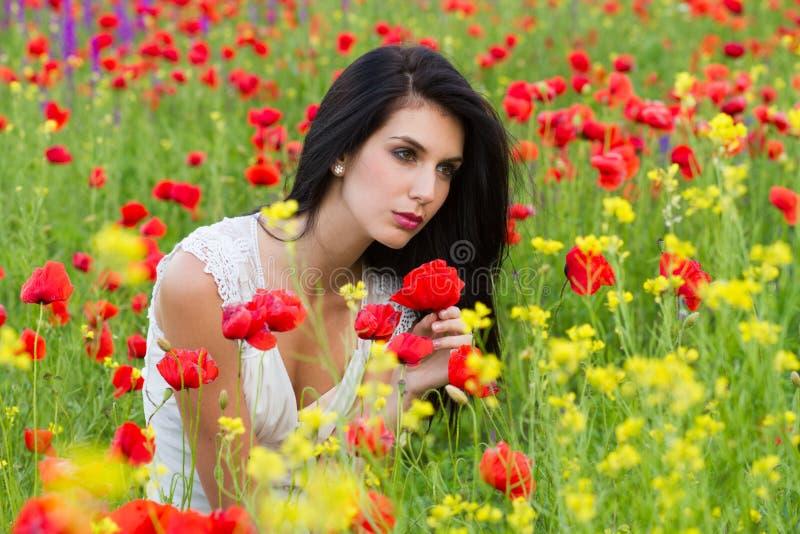 Bella ragazza che si siede nel campo del papavero fotografia stock libera da diritti