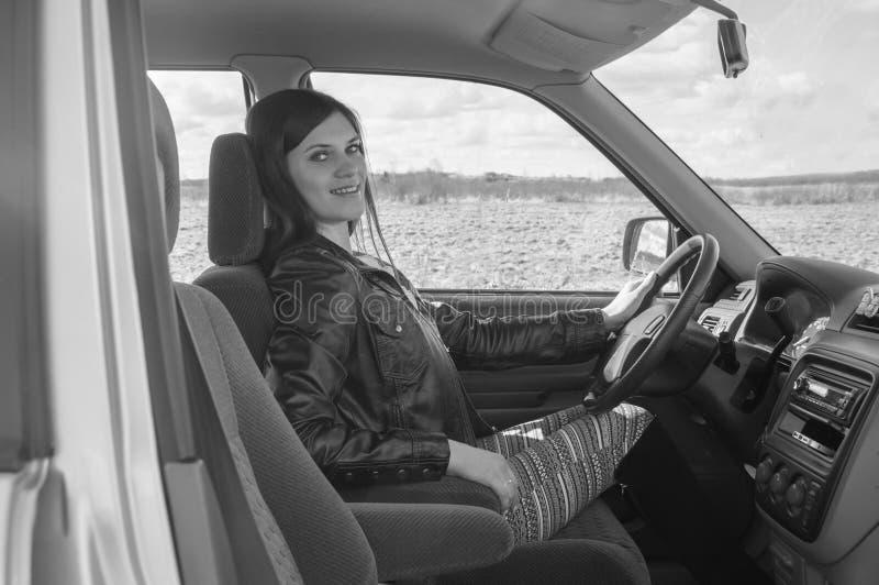 Bella ragazza che si siede nell'automobile, in bianco e nero fotografia stock