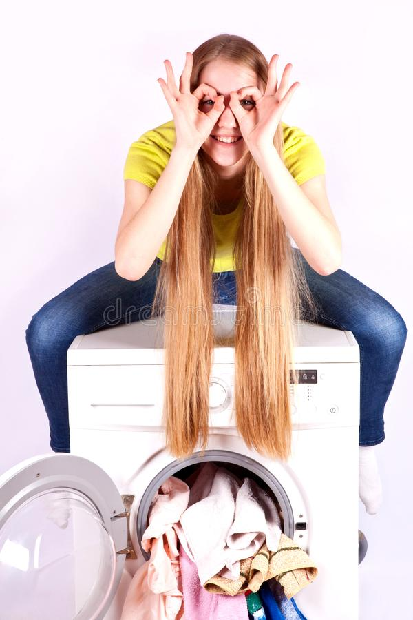 Bella ragazza che si siede sopra la lavatrice Pubblicità della lavatrice fotografia stock libera da diritti