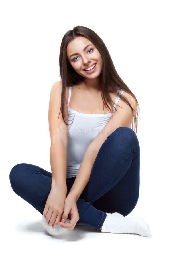 Bella ragazza che si siede su un fondo bianco isolato immagini stock