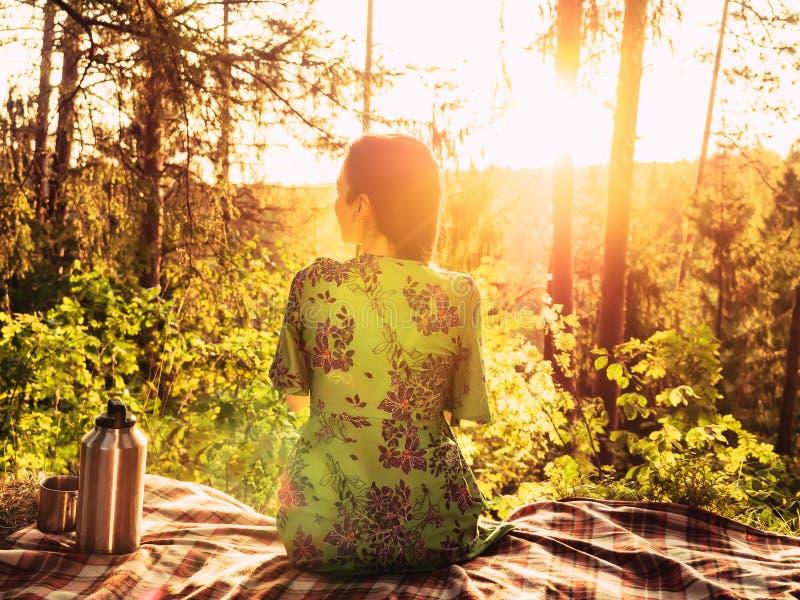 Bella ragazza che si siede su un plaid in una radura della foresta durante la luce solare luminosa di tramonto intorno alla belle fotografie stock