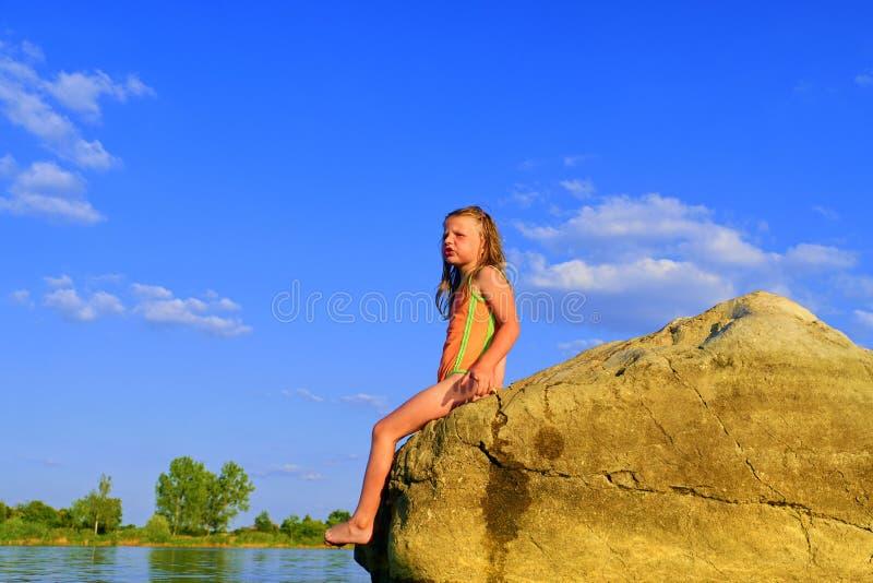 Bella ragazza che si siede su una grande roccia La bambina sta portando il costume da bagno Estate e concetto felice di infanzia  fotografie stock libere da diritti