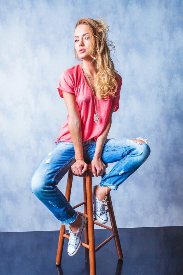 Bella ragazza che si siede su una posa di legno della sedia fotografia stock libera da diritti