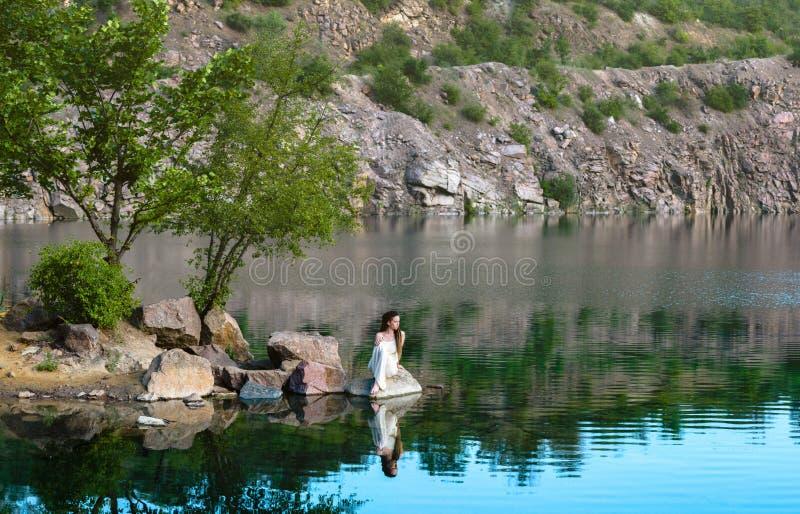 Bella ragazza che si siede su una roccia in un vestito leggero Sulla riva del lago fotografia stock libera da diritti