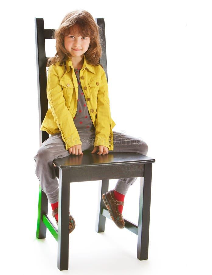 Bella ragazza che si siede su una sedia immagine stock libera da diritti