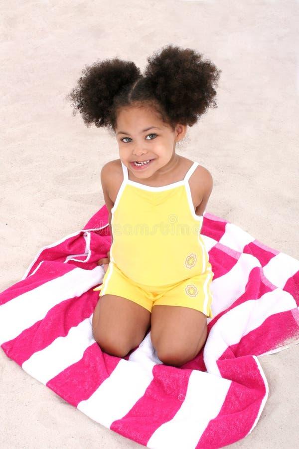 Bella ragazza che si siede sul tovagliolo di spiaggia nella sabbia immagini stock libere da diritti