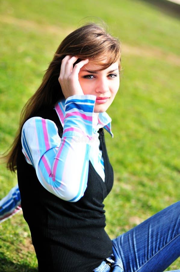 Bella ragazza che si siede sull'erba fotografia stock