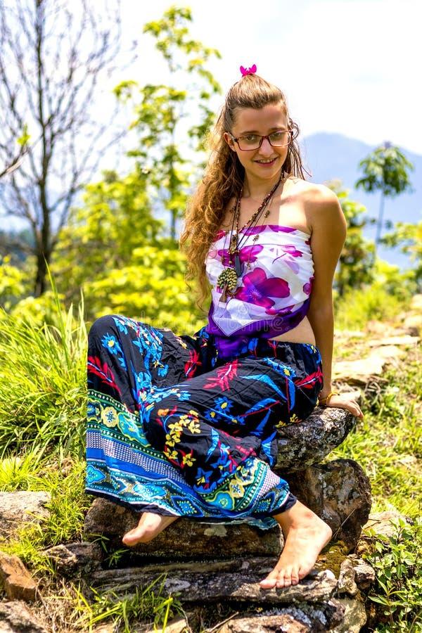 Bella ragazza che si siede sulla roccia e che posa per la foto, ragazza che porta maxi gonna floreale, fondo sorridente naturale  fotografia stock