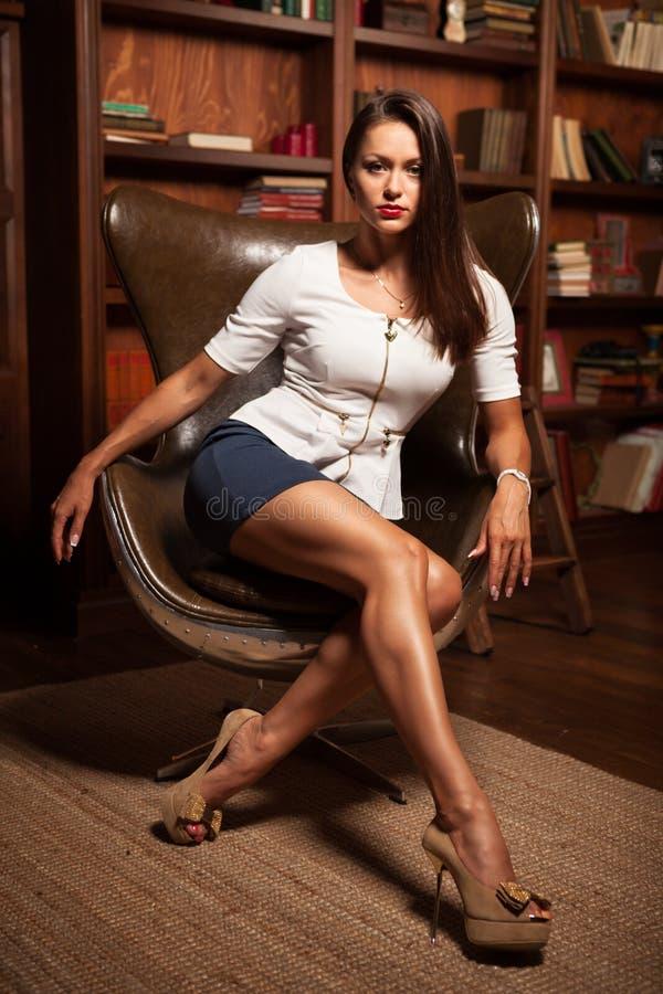 Bella ragazza che si siede in una sedia di cuoio fotografia stock