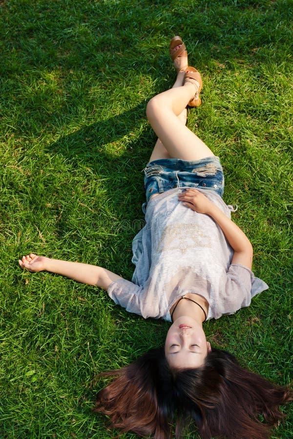 Bella ragazza che si trova giù all'erba fotografie stock libere da diritti