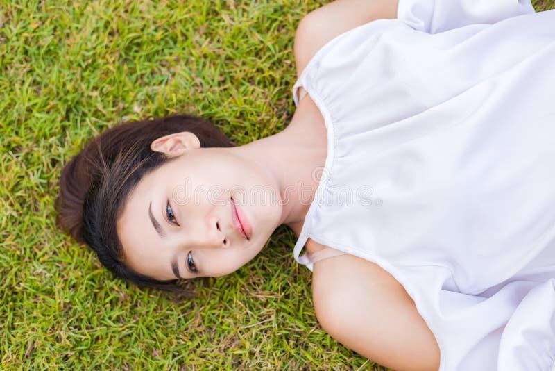 Bella ragazza che si trova giù dell'erba immagini stock libere da diritti