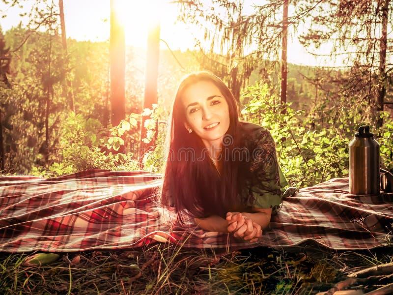 Bella ragazza che si trova su un plaid in una radura della foresta durante la luce solare luminosa di tramonto intorno alla belle immagine stock