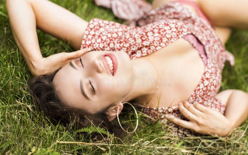 Bella ragazza che si trova sul campo Erba verde Felice e sorridere fotografia stock